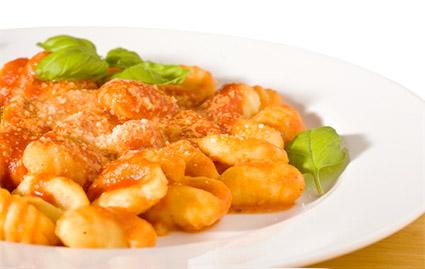 Њоки со доматен сос и пармезан, декорирани со свеж босилек